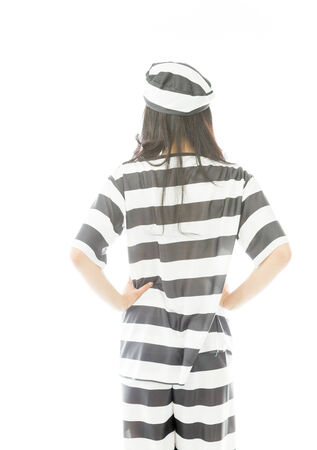 arms akimbo: Rear view of a young Asian woman standing with her arms akimbo in prisoners uniform