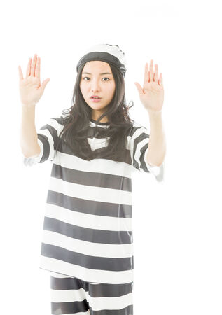 Young Asian woman making stop gesture sign from both hands in prisoners uniform photo