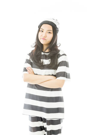 Young Asian woman standing with her arms crossed in prisoners uniform photo