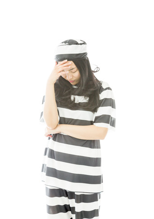 Upset young Asian woman with her head in hands in prisoners uniform photo