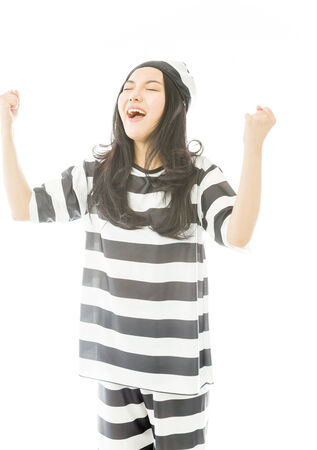 Young Asian woman celebrating success in prisoners uniform photo