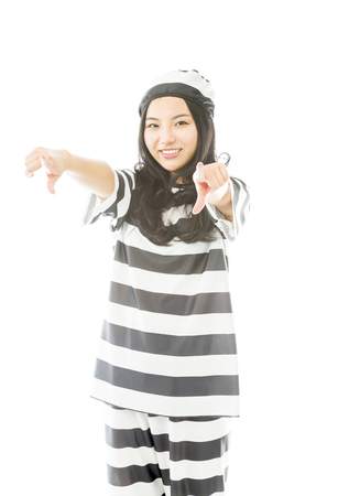 Smiling young Asian woman pointing towards camera from both hands in prisoners uniform photo