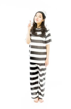Young Asian woman in prisoners uniform standing with finger crossed photo