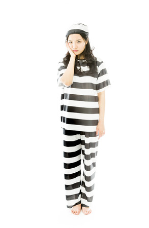 Upset young Asian woman in prisoners uniform with her hands on cheek