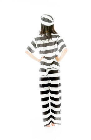 Rear view of a young Asian woman standing with her arms akimbo in prisoners uniform