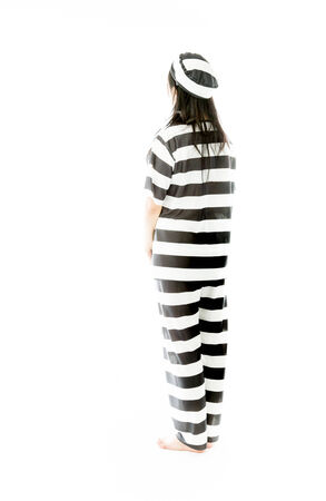 Rear view of an Asian young woman day dreaming in prisoners uniform photo