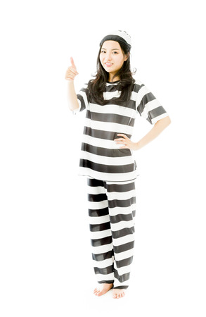 Young Asian woman showing thumb up sign in prisoners uniform photo