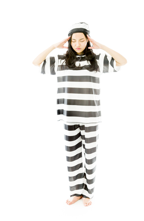 Young Asian woman suffering from headache in prisoners uniform photo