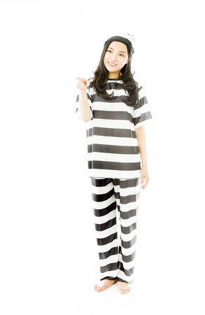 Young Asian woman showing something in prisoners uniform photo