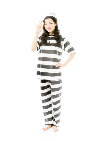 Young Asian woman showing OK sign in prisoners uniform photo