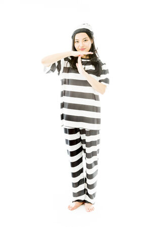 break out of prison: Young Asian woman making time out signal with hands in prisoners uniform