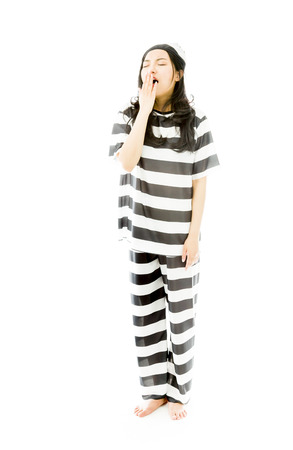 Young Asian woman yawning in prisoners uniform photo