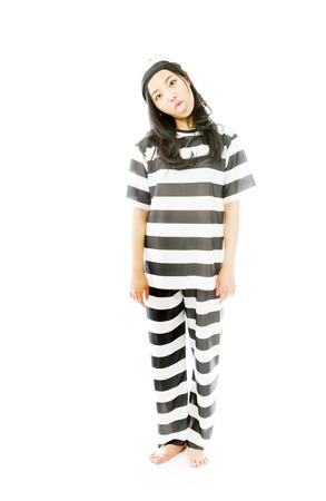 Young Asian woman sticking out her tongue in prisoners uniform photo