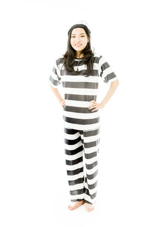 arms akimbo: Young Asian woman standing with her arms akimbo in prisoners uniform Stock Photo