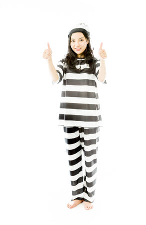 Smiling young Asian woman showing thumb up sign with both hands prisoners uniform photo