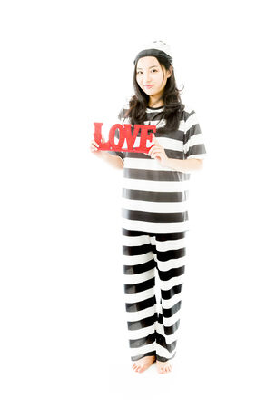 Asian young woman holding a red LOVE text in prisoners uniform photo