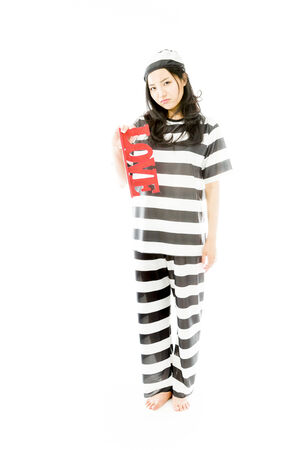 Sad Asian young woman holding a red LOVE text in prisoners uniform photo
