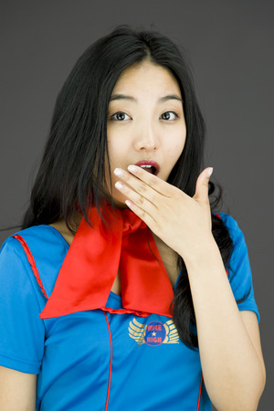 mouth close up: Shocked Asian air stewardess with hand over mouth