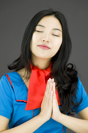 clasped: Asian air stewardess praying with her hands clasped