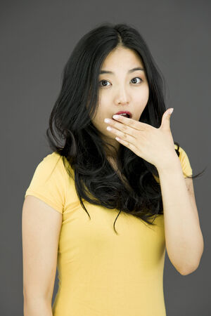 raised eyebrows: Young Asian woman with shocked expression