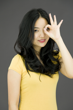 Young Asian woman showing OK sign photo