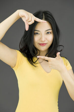 Young Asian woman making frame with fingers photo