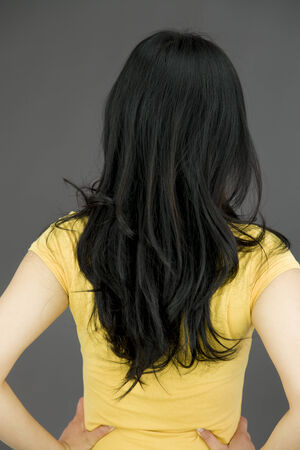 arms akimbo: Rear view of a young Asian woman with her arms akimbo