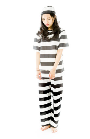 Sad handcuffed Asian young woman in prisoners uniform