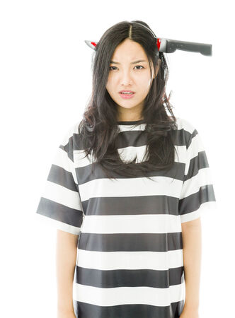 Sad Asian young woman wearing knife shaped hair band in prisoners uniform photo