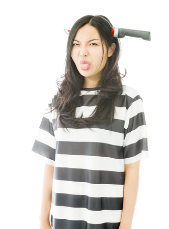 Asian young woman wearing knife shaped hair band in prisoners uniform and sticking her tongue out photo