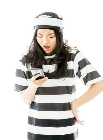 send to prison: Shocked young Asian woman text messaging on a mobile phone in prisoners uniform