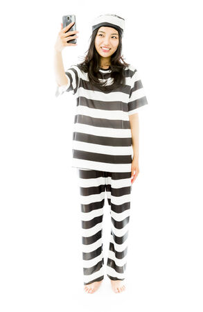 criminal activity: Asian young woman photographing herself with her mobile phone in prisoners uniform Stock Photo