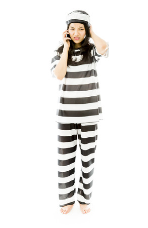 Frustrated young Asian woman talking on a mobile phone in prisoners uniform