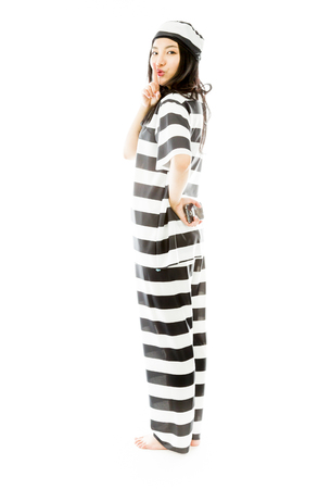 Young Asian woman standing with finger on lips in prisoners uniform photo