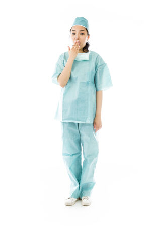 Shocked Asian female surgeon with hand over mouth isolated on white background photo