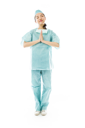 clasped: Asian female surgeon praying with hands clasped