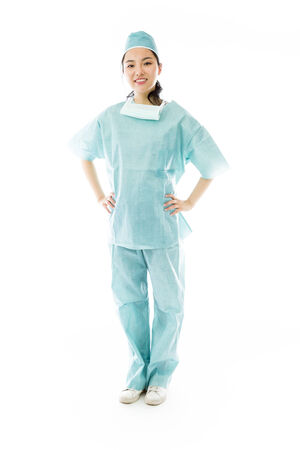 arms akimbo: Confident Asian female surgeon standing with arms akimbo Stock Photo