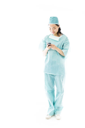 Asian female surgeon text messaging on a mobile phone photo