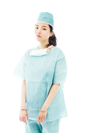 handcuffed hands: Asian female surgeon in blue uniform with handcuffed hands