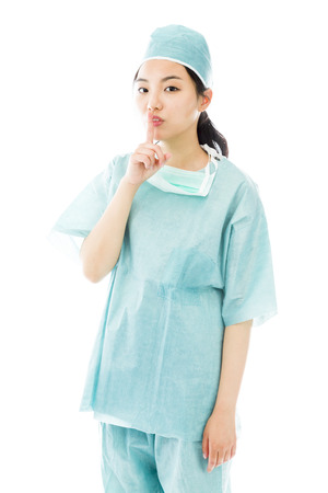 Asian female surgeon with finger on lips