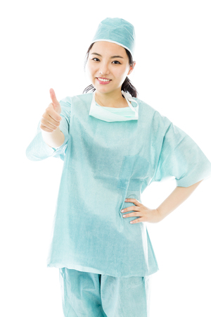 Asian female surgeon making thumbs up sign standing with hand on hip photo