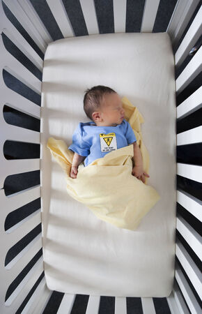 High angle view of a newborn baby sleeping in a crib photo