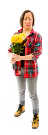Worried young woman holding bouquet of sunflowers photo