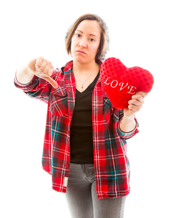fully unbuttoned: Young woman holding heart shape and showing thumbs down sign