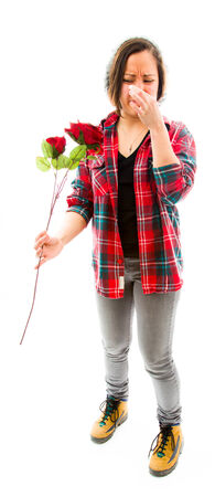 Young woman pinches her nose with holding rose photo