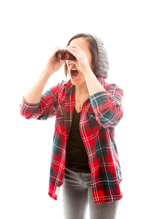 Young woman looking through binoculars and shock photo