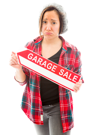 Worried saleswoman holding a garage sale sign photo
