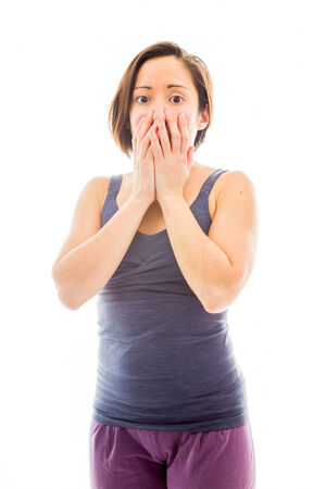 Young woman with hand over her mouth and shock photo