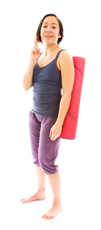 crossing fingers: Young woman carrying exercise mat wishing with crossing fingers