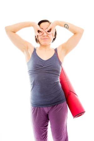 Young woman carrying exercise mat with her hands around her eyes photo